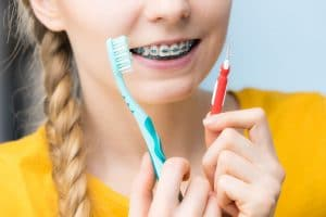 Woman-smiling-cleaning-teeth-with-braces-977255956_2124x1417