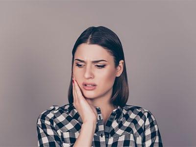 mujer que sostiene lado de la cara de dolor