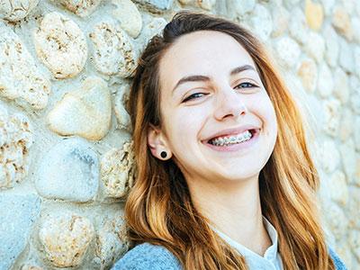 Muchacha adulta joven sonriente con los apoyos